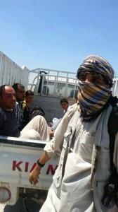 IS terrorist in front of captured civilians in Shingal