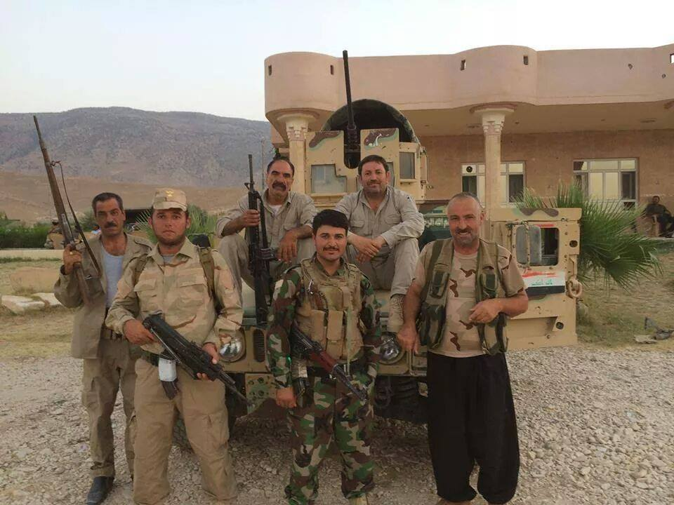 Ezidi fighters in front of a Humvee seized from ISIS terrorists