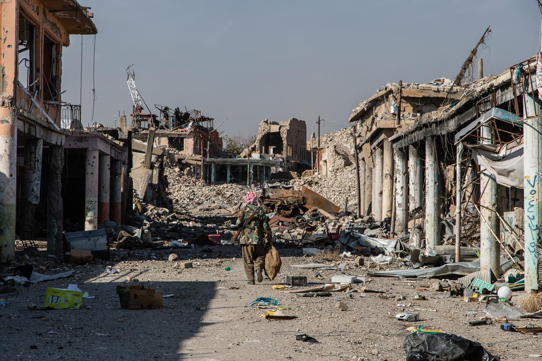 An Ezidi resistance fighters walks through the ruins of Shingal city (Hawre Khalid/AJ)