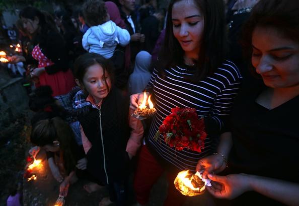 ÊzîdInnen tragen das heilige Cira-Licht in Lalish am Neujahrstag im Jahr 2015 (Safin Hamed/AFP)