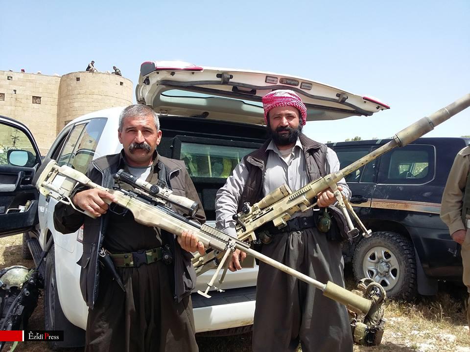 Abu Hassan (li.) und Qasim Khalaf, K.S.-HPŞ Kämpfer, posieren mit panzerbrechenden Scharschützengewehren französischer Militärberater im Shingal-Gebirge. Selbst kämpfen sie seit Monaten mit leichten Maschinengewehren