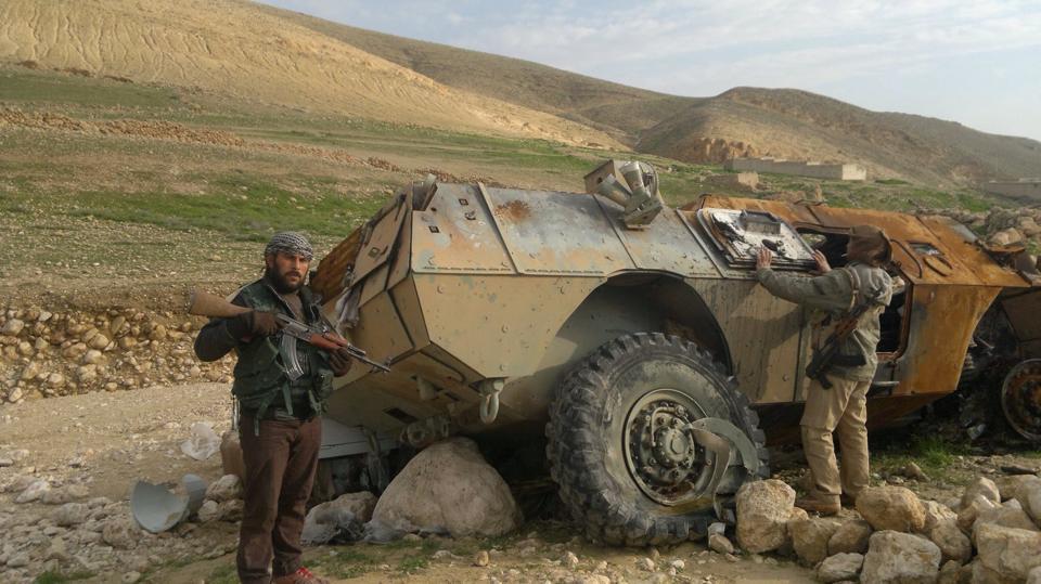 Êzîdîsche Widerstandskämpfer vor einem abgebrannten gepanzerten Fahrzeug der IS-Terrormiliz in Shingal