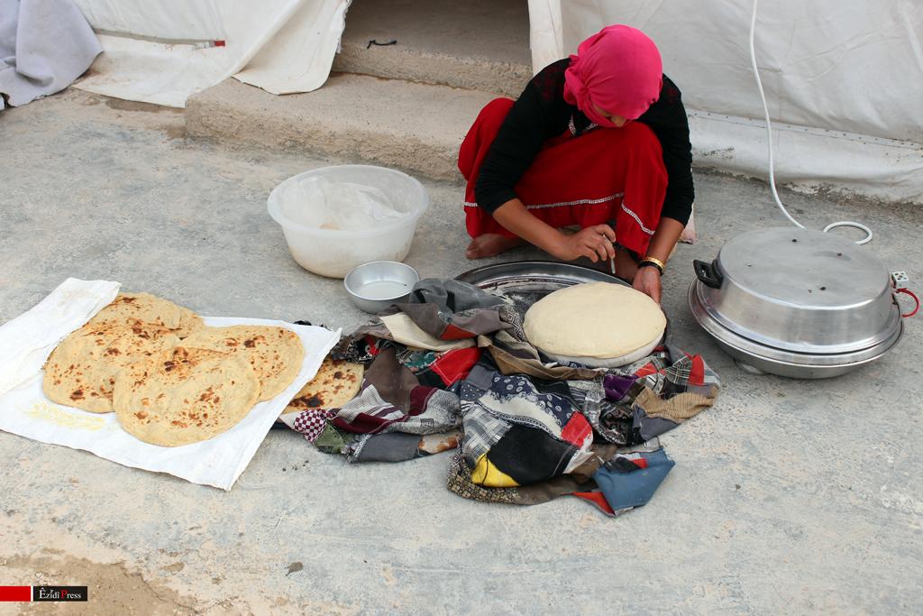 Êzîdîsche Mutter backt Brot vor ihrem Zelt im Flüchtlingslager von Sharya
