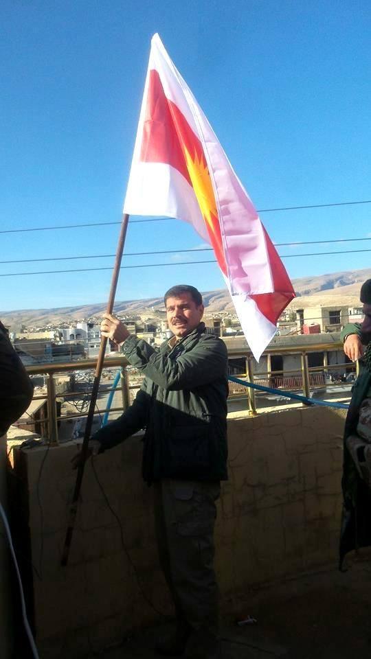 Heydar Shesho, Oberkommandeur der HPÊ, hisst am neuen Stützpunkt die Widerstandsflagge der Êzîden (Januar, 2016)