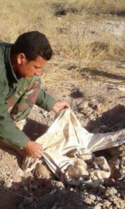 Ein Peshmerga inspiziert die Kleidung in dem entdeckten Massengrab in Shababit