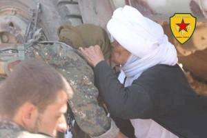 Kämpfer der YPG versorgen eine êzîdîsche Frau im Gebirge mit Wasser